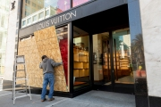 A worker installs plywood over the windows of  the Louis Vuitton store downtown  San Francisco, CA, on March 20, 2020. The luxury store had its windows covered with plywood to discourage looting. California residents were ordered to stay home to slow the spread of the coronavirus as part of a lockdown effort.