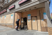 An pedestrian enters the local Walgreens covered with  plywood  to discourage looting in San Francisco on March 31, 2020 . Millions of San Francisco Bay Area  residents were ordered to stay home for the third week to slow the spread of the coronavirus as part of a lockdown effort.