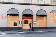 An pedestrian walks by the Italian restaurant, Tratto, that is covered with plywood  to discourage looting in San Francisco on March 31, 2020 . Millions of San Francisco Bay Area  residents were ordered to stay home for the third week to slow the spread of the coronavirus as part of a lockdown effort.