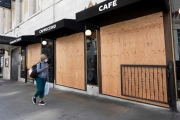 An pedestrian walks by a Starbucks Coffee  that is covered with plywood  to discourage looting in San Francisco on March 31, 2020 . Millions of San Francisco Bay Area  residents were ordered to stay home for the third week to slow the spread of the coronavirus as part of a lockdown effort.