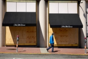 An pedestrian walks by the Saks Fifth Avenue luxury store that is covered with plywood  to discourage looting in San Francisco on March 31, 2020 . Millions of San Francisco Bay Area  residents were ordered to stay home for the third week to slow the spread of the coronavirus as part of a lockdown effort.