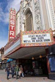 Pedestrians walk past the Castro Theater on Castro Street in San Francisco, California, U.S., on  March 18, 2020. Millions of San Francisco Bay Area  residents were ordered to stay home to slow the spread of the coronavirus as part of a lockdown effort, marking one of the nation's strongest efforts to stem the spread of the deadly virus.