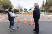 Local KCBS radio reporter Holly Quan uses a long plastic  tube to hold her microphone so she can keep a safe distance from  Hayward Fire Captain Don Nicholson during an interview at the COVID-19 testing center in Hayward, CA, on March 23, 2020.  The free test facility opened to  to the public this morning regardless of where the patients live or their immigration status. The entire state of California is on a shelter-in-place status ordered by the governor to slow the spread of the COVID-19 disease.