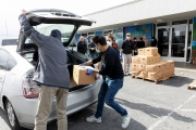 Members of the Hope Ministries Church load a box of food in a car at a drive-through food distribution in South San Francisco, CA, on April 8, 2020.  The food drive was organized to help families in need during the COVID-19 pandemic.