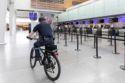 A policeman rides his bicycle through the empty terminal the San Francisco International airport on April 8, 2020. The COVID-19 pandemic has reduced air traffic tremendously.