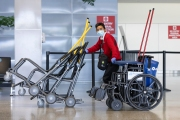 An airport employee with a mask and gloves pushes wheelchairs through the empty terminal the San Francisco International airport on April 8, 2020. The COVID-19 pandemic has reduced air traffic tremendously.