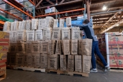 "A volunteer stacks up bags of food at the Alameda Food Bank distribution center in Alameda, CA, on April 15, 2019. The food was distributed later through a drive-through to people in need following the loss of their jobs due to the ""shelter-in-place"" order to limit the spread of the coronavirus SARS-CoV-2."