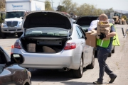 "A volunteer loads bags of food into the trunk of car  at the Alameda Food Bank distribution center in Alameda, CA, on April 15, 2019. The food was distributed  through a drive-through to people in need following the loss of their jobs due to the ""shelter-in-place"" order to limit the spread of the coronavirus SARS-CoV-2."