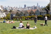 People enjoy a sunny and warm day at the Alamo Square Park in san Francisco, CA, on April 25, 2020, despite a current shelter-at-home order due to COVID-19 .  On the right are the famous houses bettie known as the Painted Ladies.