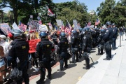 Police officers prevent protesters from entering the California State Capitol in Sacramento, CA, on May 1, 2020.