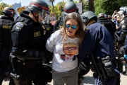 Police officers arrest a  protester n front of the California State Capitol in Sacramento, CA, on May 1, 2020.