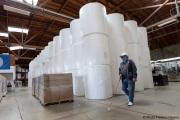A blind worker walks by 1,000-pound rolls of toilet paper inside the Sirkin Center in San Leandro, CA, on May 11, 2020.