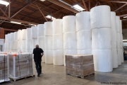 A sighted worker walks by 1,000-pound rolls of toilet paper inside the Sirkin Center in San Leandro, CA, on May 11, 2020.