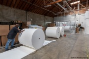 A  sighted worker pushes 1,000-pound rolls of toilet paper towards the production line of toilet paper packets inside the Sirkin Center in San Leandro, CA, on May 11, 2020.