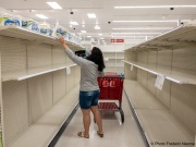 A woman picks up one of few roll of toilet paper for sale at a  Target store in San Leandro, CA, on May 11, 2020. Toilet paper is still difficult to find while six San Francisco Bay Area counties remain under a shelter-in-place order until the ned of May.