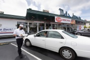 A waiter or carhop brings a meal to a customer waiting in his car at the Mel's  Drive-In restaurant in San Francisco, CA, on May 12, 2020.Like in the 1950's, Mel's Drive-In restaurant in San Francisco is now offering carhop service so customers stay safe while still feeling like they get the experience of eating out during the shelter-in-place order due to the coronavirus pandemic.