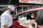 A waiter or carhop brings a meal to  customers waiting in their car at the Mel's  Drive-In restaurant in San Francisco, CA, on May 12, 2020.Like in the 1950's, Mel's Drive-In restaurant in San Francisco is now offering carhop service so customers stay safe while still feeling like they get the experience of eating out during the shelter-in-place order due to the coronavirus pandemic.