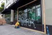 Workers boarding up stores in Oakland, CA, on May 30, 2020, after some were broken into and looted following violent  protests the night before.