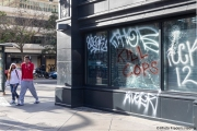 A couple  walks by a local store in Oakland, CA, on May 30, 2020,, that had its storefront smashed and filled with graffitti.