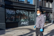 A store owner stands in front of his  store in Oakland, CA, on May 30, 2020,, that had its storefront smashed and filled with graffitti.