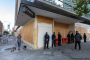 Police officers stand guard in front of Chase bank  in Oakland, CA, on May 30, 2020, that had its storefront boarded up following violent  protests the night before.