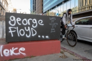 A man rides his bicycle  in Oakland, CA, on May 30, 2020, by wood boards with graffiti in support of  George Floyd in Minneapolis, MN, who passed away while pleading with arresting officers that he couldn't breathe as one of the officers was shown on video kneeling on his neck.
