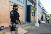 A private security guard stands in front of the Mercedes-Benz dealership   in Oakland, CA, on May 30, 2020 with workers boarding up the storefront that was smashed during violent  protests the night before.
